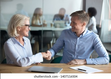 Happy male client customer employee partner handshake old broker boss hr manager sign insurance job contract agreement take bank loan buy services shake hands getting hired at office business meeting