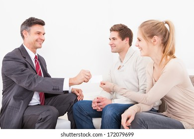 Happy Male Consultant Giving Visiting Card To Young Couple