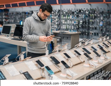 Happy male customer choosing smartphone in the mobile phone shop. difficult decision. Various choice. He is smiling