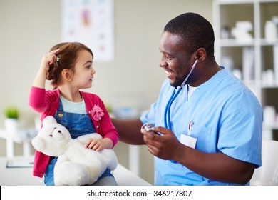 Happy male doctor communicating with child in clinic
