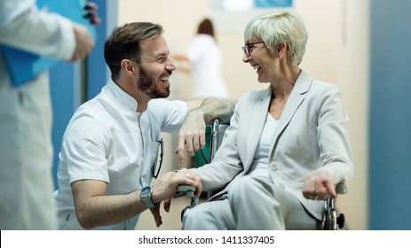 Happy male doctor communicating with mature patient who is in wheelchair in a hallway at clinic.