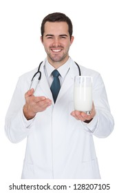 Happy Male Doctor Holding Glass Of Milk. Isolated On White