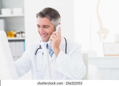 Happy male doctor using landline phone in clinic