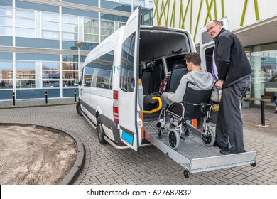 Happy male driver assisting passenger in wheelchair to board taxi outside building