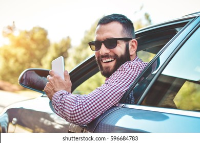 Happy male driver smiling while sitting in a car with open front window