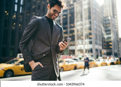 Happy male entrepreneur in formal clothes received funny message on smartphone strolling on New York street.Successful businessman reading incoming notification with good financial news on cellular