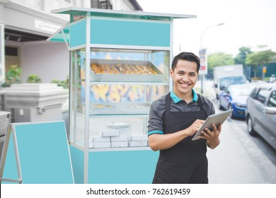 happy male entrepreneur with his newly open small business food stall. promoting online using tablet pc