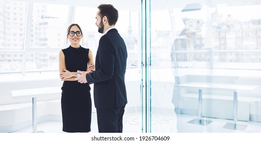 Happy male and female business partners enjoying collaborative brainstorming and friendship during working time in office company, smiling employees in formal clothes have positive conversation