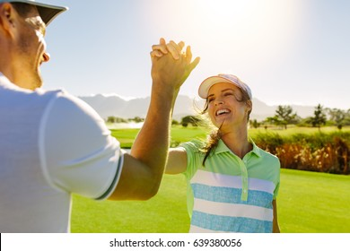 Happy male and female friends giving high-five at golf course after the game. Pro golfer enjoying the game on field and shaking hands.