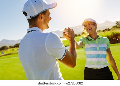 Happy male and female friends shaking hands at golf course after the game. Pro golfer enjoying the game on field.