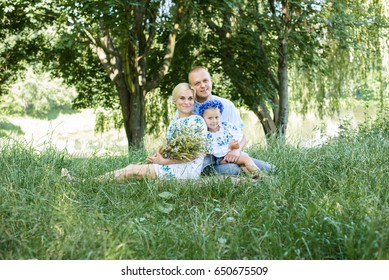 Happy male and female playing with daughter outside