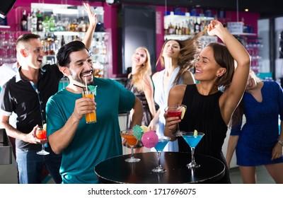 Happy-Männchen mit Weibchen sprechen und trinken Cocktails auf der Party im Club