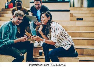 Happy male and female teen students share multimedia files online via smartphones during meeting in college, skilled positive multiracial crew of employees using technologies for research together