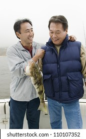 Happy male friends with a catch on a fishing boat