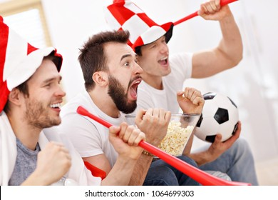 Happy male friends cheering and watching sports on tv