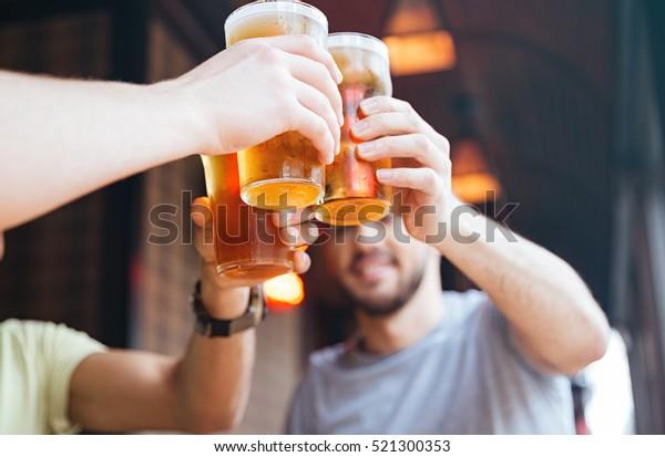 Amigos masculinos felizes tilintando com canecas de cerveja no pub