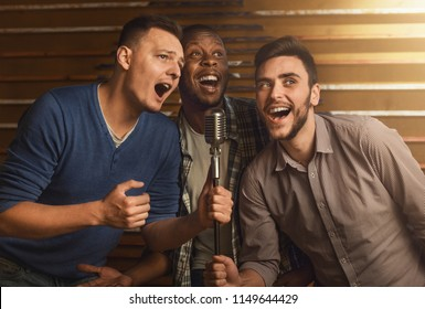 Happy male friends singing karaoke together in bar