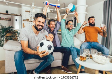 Happy male friends with vuvuzela wearing black face protective mask watching football at home