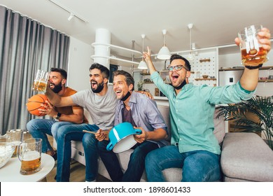 Happy male friends  wearing black face protective mask watching basketball at home