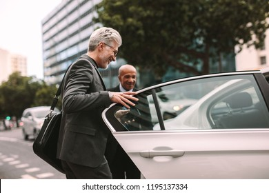 Happy male getting into a cab. Businessman entering a taxi on city street.