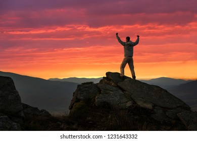 Happy male hiker on mountain top at sunset