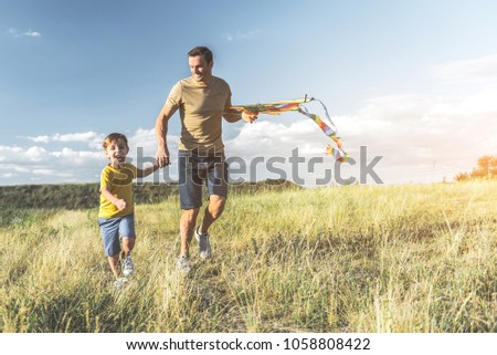 40d0a0e4 happy male with kite and boy running on sunlit meadow and holding hands.  Full length