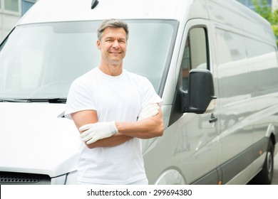 Happy Male Painter With Arms Crossed Standing In Front Of Van