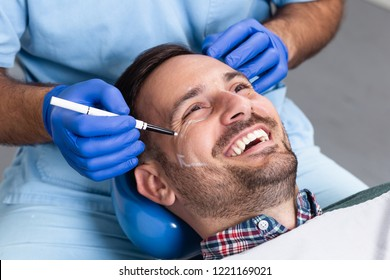 Happy male patient with correction lines on the face in an examination room.