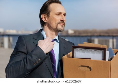 Happy male person holding box with documents