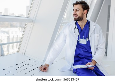 Happy male physician resting near window