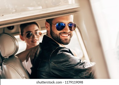fa98049747 happy male pilot in sunglasses and leather jacket looking at camera while  his girlfriend sitting near