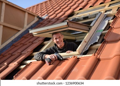 "happy male roofer is building new skylight in roof with red tiles, brand ""velux"" roof area window"