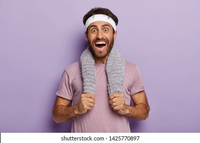 Happy male runner smiles broadly, surprised to cover long distance on marathon, has towel on neck, wears casual t shirt and white headband, isolated over purple background. Sport and training concept