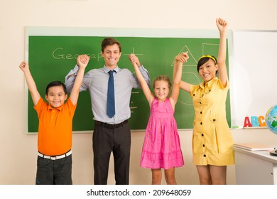 Happy male school teacher and his pupils posing in the classroom