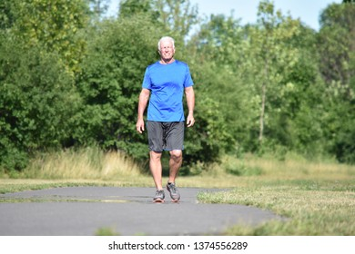 Happy Male Senior Grandfather Wearing Sneakers Walking In Park