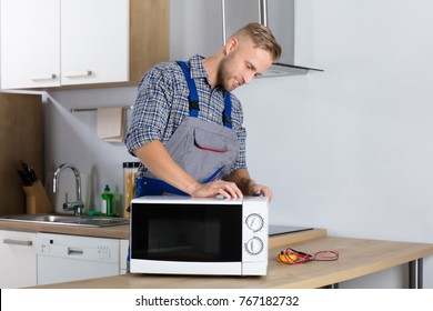 Happy Male Serviceman Using Screwdriver To Repair Microwave In Kitchen At Home