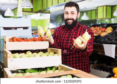 Happy male shop assistant demonstrating pears in grocery shop