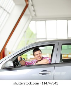 Happy male sitting in his automobile and holding a car key
