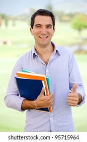Happy male student with thumbs up holding a notebook