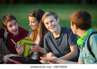 Happy male teen sitting with students outdoors