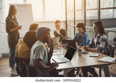 Happy male telling by mobile while situating at desk near beaming colleagues during conference in office. Glad lady standing near board