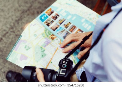 Happy male tourist in city with camera and map