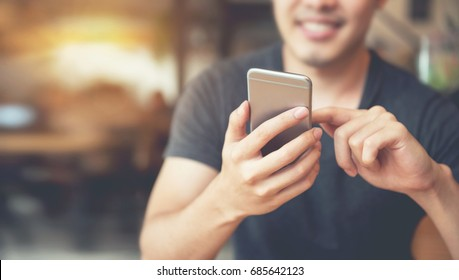 Happy male using smartphone at modern coffee shop, he chatting Online Messaging on mobile.