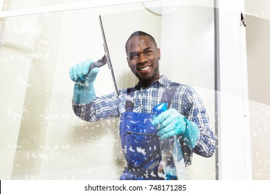 Happy Male Worker Cleaning Glass With Squeegee And Spray Bottle