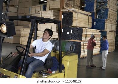 Happy male worker driving fork truck in warehouse