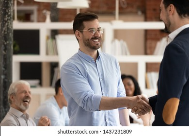 Happy male worker feel excited get promoted rewarded being best employee handshake manager praising apprecitaing thanking for good work in office, staff reward, trust, recognition and respect concept