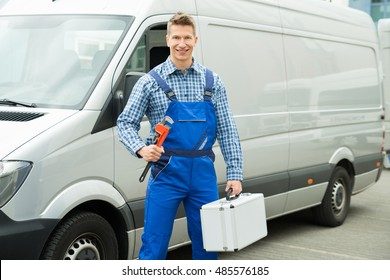 Happy Male Worker With Work Tool And Toolbox In Front Of Van
