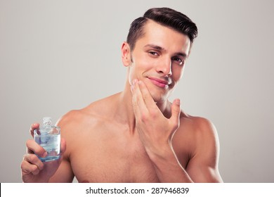 Happy man applying lotion after shave on face over gray background