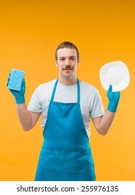 happy man in apron holding clean dishes and sponge, against yellow background