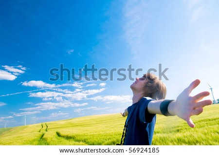 Happy man with arms up on summer lanscape